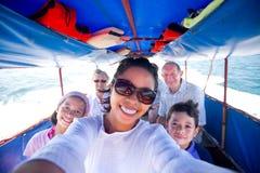 Familia que monta un barco gordo que va a una isla. fotografía de archivo libre de regalías