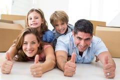 Familia que muestra los pulgares para arriba en nueva casa Imagen de archivo libre de regalías
