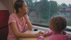 Familia que pasa el tiempo en viaje de tren en Asia, mirando a la ventana y a hablar almacen de metraje de vídeo