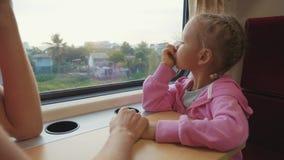 Familia que pasa el tiempo en viaje de tren en Asia, mirando a la ventana y a hablar metrajes