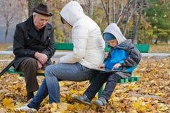 Familia que pasa un día del otoño en el parque Imagen de archivo