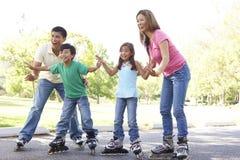 Familia que patina en el parque Foto de archivo libre de regalías