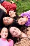 Familia que pone en la hierba Fotos de archivo libres de regalías