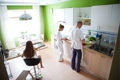 Familia que prepara el desayuno Foto de archivo libre de regalías