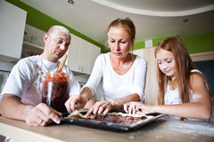 Familia que prepara el desayuno Imagenes de archivo