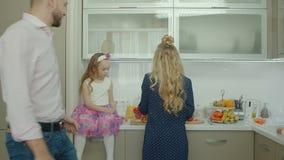 Familia que prepara el desayuno junto en cocina almacen de metraje de vídeo