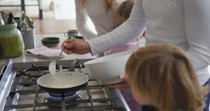 Familia que prepara la comida en la cocina en casa 4k almacen de video