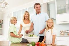 Familia que prepara la ensalada en cocina moderna Fotografía de archivo