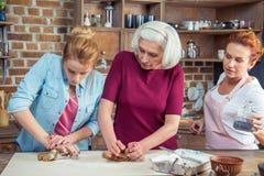 Familia que prepara las galletas del pan de jengibre Imagen de archivo