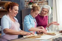 Familia que prepara las galletas del pan de jengibre Foto de archivo