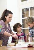 Familia que prepara talud de la magdalena en cocina Imágenes de archivo libres de regalías