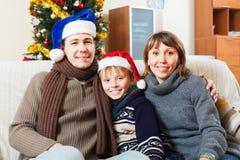 Familia que presenta con el árbol de navidad Foto de archivo libre de regalías