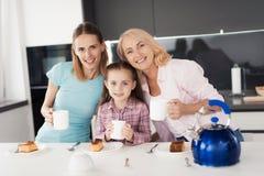 Familia que presenta en la cocina con las tazas de té en manos Miran la cámara y sonríen Imagen de archivo libre de regalías