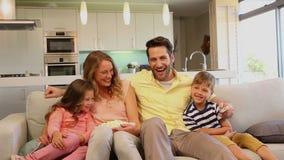 Familia que ríe en el sofá almacen de video