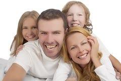 Familia que ríe junto mientras que pone en la cama cubierta con blanco Fotos de archivo