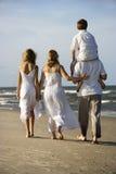 Familia que recorre abajo de la playa. Foto de archivo