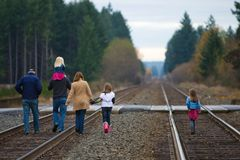 Familia que recorre abajo de pistas del tren Imagen de archivo