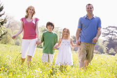 Familia que recorre al aire libre celebrando la sonrisa de la flor Fotografía de archivo