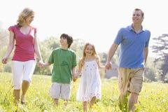 Familia que recorre al aire libre celebrando la sonrisa de la flor Fotografía de archivo libre de regalías