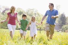 Familia que recorre al aire libre celebrando la sonrisa de las manos Foto de archivo