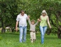Familia que recorre al aire libre llevando a cabo las manos Imagen de archivo libre de regalías