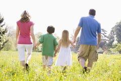 Familia que recorre al aire libre llevando a cabo las manos Foto de archivo libre de regalías