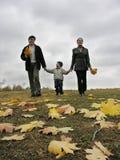 Familia que recorre con las hojas y las nubes de otoño Imagenes de archivo