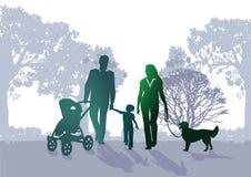 Familia que recorre en el parque Foto de archivo