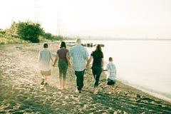 Familia que recorre en la playa Foto de archivo libre de regalías