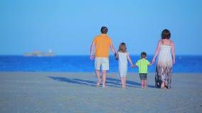 Familia que recorre en la playa metrajes