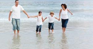 Familia que recorre en la playa Foto de archivo