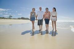 Familia que recorre en las manos de la explotación agrícola de la playa Foto de archivo libre de regalías