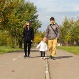 Familia que recorre en un parque imagen de archivo libre de regalías