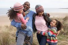 Familia que recorre a lo largo de las dunas en la playa del invierno Imágenes de archivo libres de regalías