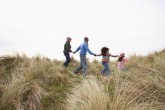 Familia que recorre a lo largo de las dunas en la playa del invierno imagenes de archivo