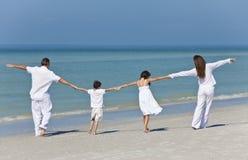 Familia que recorre y que lleva a cabo las manos en la playa Fotografía de archivo libre de regalías