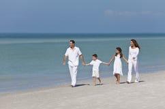 Familia que recorre y que lleva a cabo las manos en la playa Foto de archivo libre de regalías
