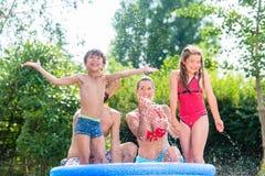 Familia que refresca abajo salpicar el agua en piscina del jardín Fotos de archivo libres de regalías