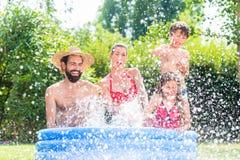 Familia que refresca abajo salpicar el agua en piscina del jardín Imagen de archivo