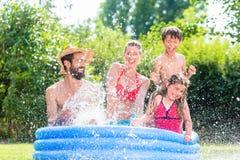 Familia que refresca abajo salpicar el agua en piscina del jardín Imagenes de archivo