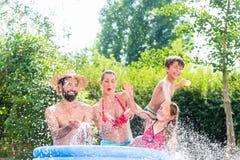Familia que refresca abajo salpicar el agua en piscina del jardín Fotografía de archivo