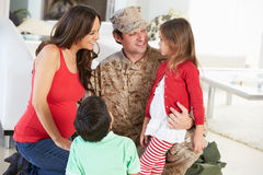 Familia que saluda al padre militar Home On Leave Imagen de archivo libre de regalías