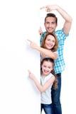 Familia que señala por el finger a la bandera imagen de archivo