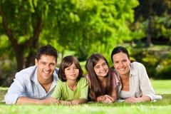 Familia que se acuesta en el parque Imagen de archivo