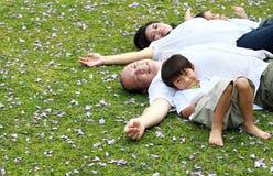 Familia que se acuesta en el parque Fotos de archivo