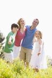 Familia que se coloca al aire libre que celebra la sonrisa de las manos Imagenes de archivo