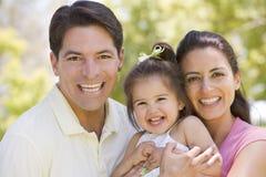 Familia que se coloca al aire libre sonriente Imagenes de archivo