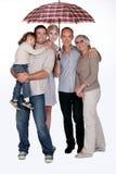 Familia que se coloca debajo del paraguas Imagen de archivo