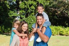 Familia que se coloca delante de árboles Imágenes de archivo libres de regalías
