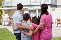 Familia que se coloca delante de su casa Fotografía de archivo libre de regalías
